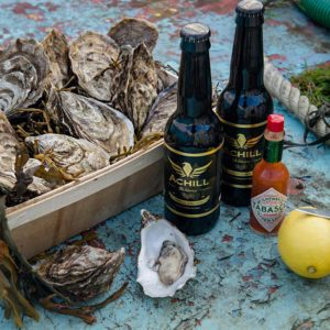 Gift box with Achill brewery beer, shucked oyster, lemon and tobasco sauce on the sole of the boat